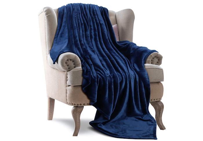 plush deep blue fleece throw blanket draped over a pale gray armchair