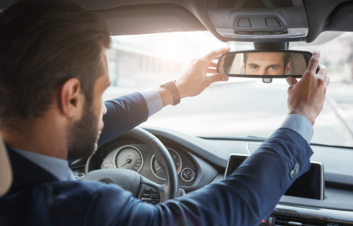 Back view of young and handsome bearded businessman in formal wear adjusting the rearview mirror while driving his car.