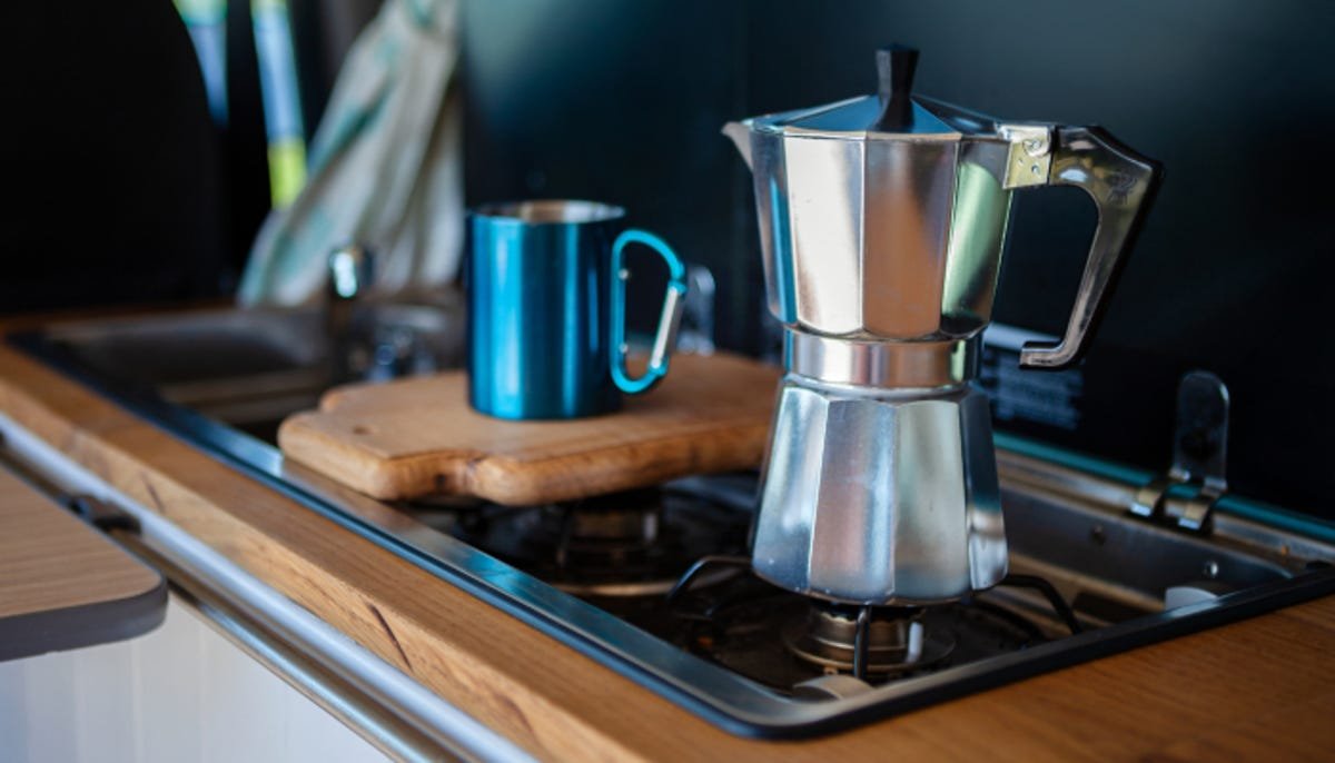 a silver stovetop coffee maker and mug on a gas cooker