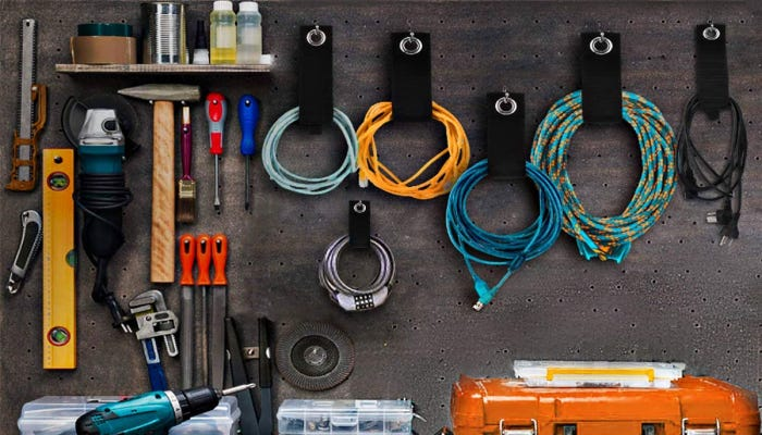 organized cords being held in holders hanging on a garage wall with tools nearby