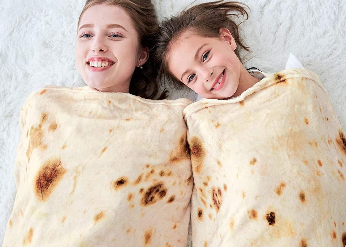 two smiling girls wrapped in tortilla-printed blankets like burritos
