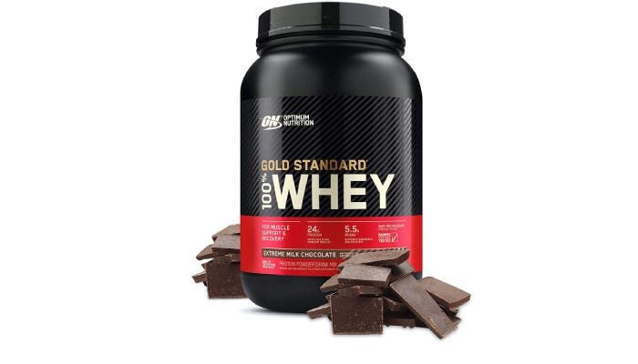 a large container of Optimum Nutrition Gold Standard whey protein powder with chocolate pieces stacked around it