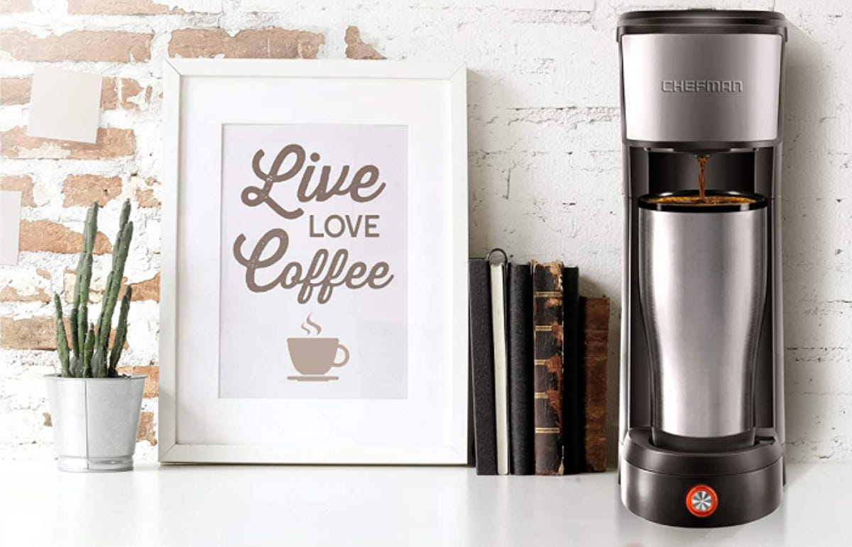 """a stainless steel tumbler is filling with coffee pouring from a single-serve coffee maker on a countertop. Nearby is a framed piece of art that says """"Live Love Coffee."""""""