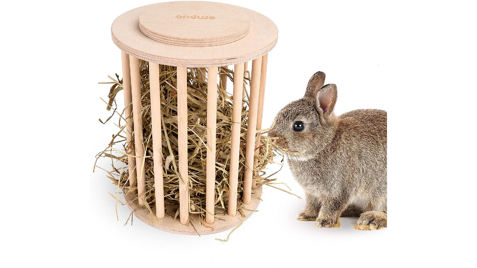 A brown bunny eating out of a round wooden hay feeder.