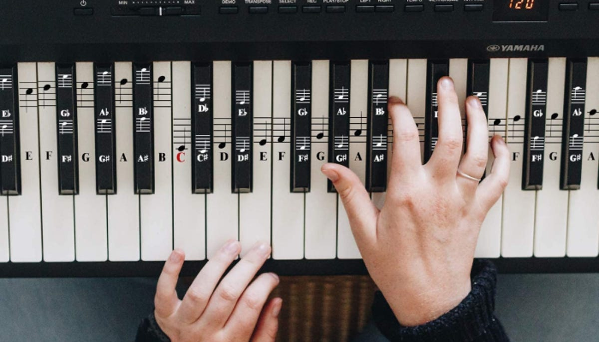 overhead shot of hands playing the piano with note stickers placed on each key