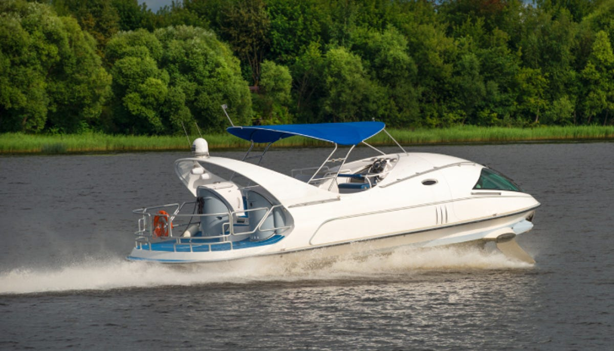 A hydrofoil boat moves at high speed along the river