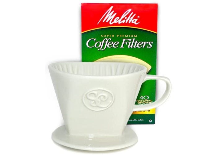 Ceramic single-serve pour-over coffee device shaped like a mug with a box of 40 paper filters behind it