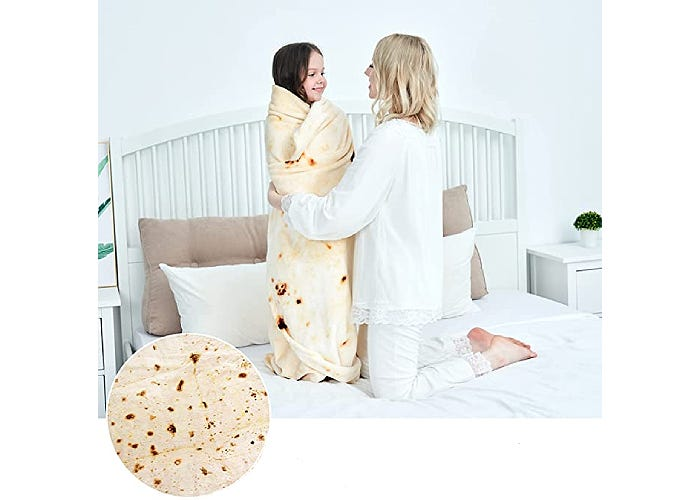 mother wrapping her daughter in burrito blanket on bed