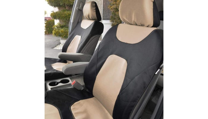 Two-tone cream and black car covers are shown on the two front seats of a car, which has one door open. The seat covers do not cover the arm rests.