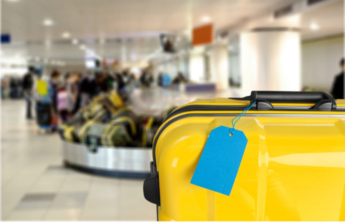 luggage tag on a suitcase with baggage claim area at an airport in the background