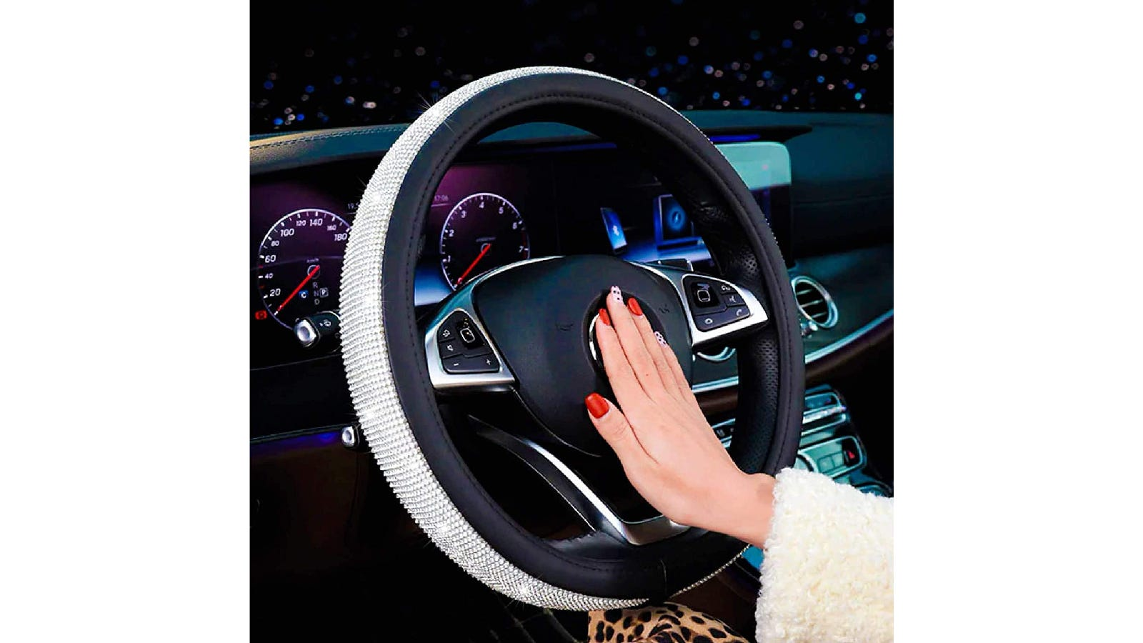 A steering wheel with a black cover that has white rhinestones around the outside edge.