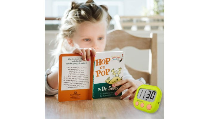Little girl reading a book with a timer placed to her left