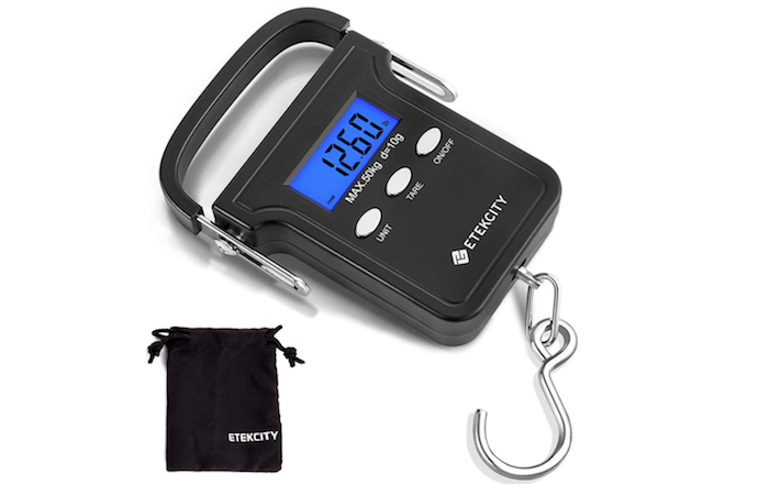 A handheld square shaped luggage scale with curved handle, metal hook and black carrying case.