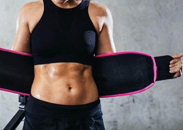 A woman stretching a black and pink waist trainer behind her back.