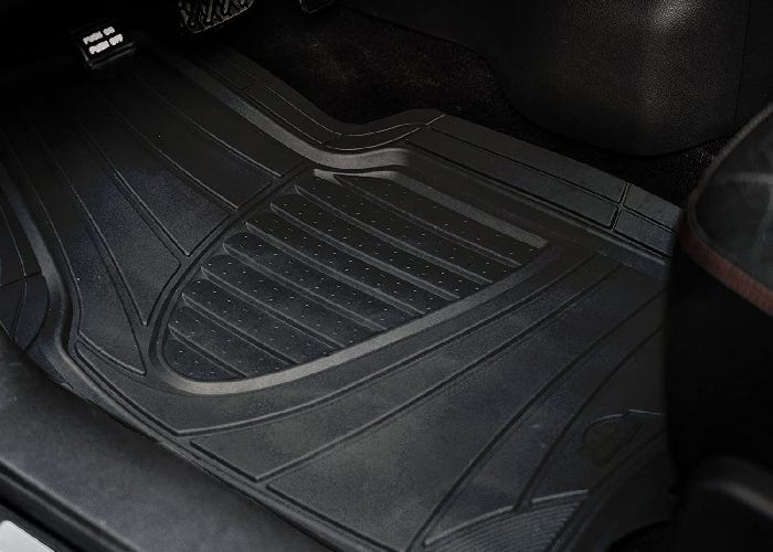 A rubber car mat over the floor of the driver's seat.