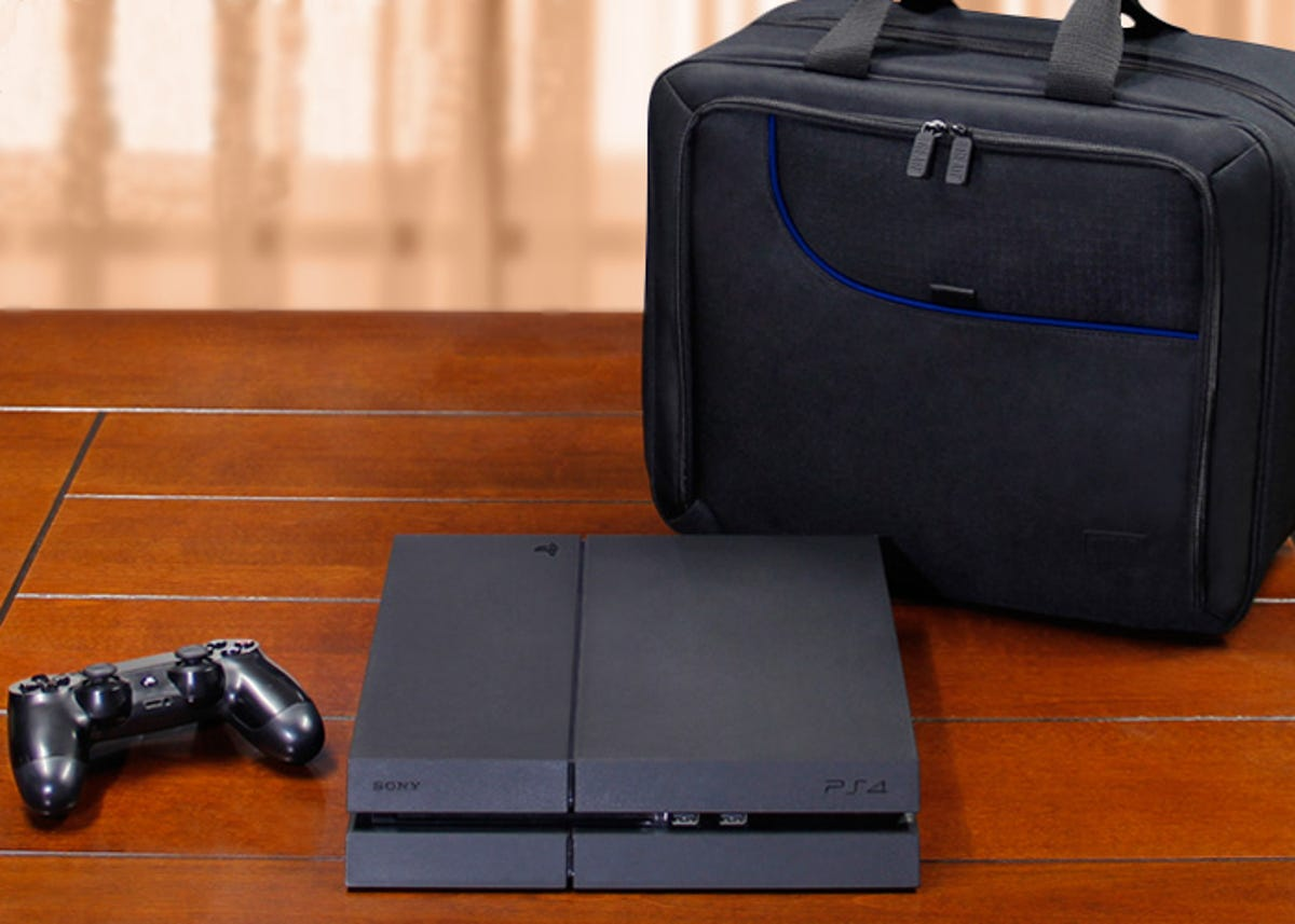 a playstation with a controller on a table and a carrying case next to it