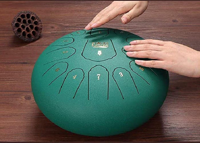 A green tongue drum with thirteen notes played by tapping with two hands.