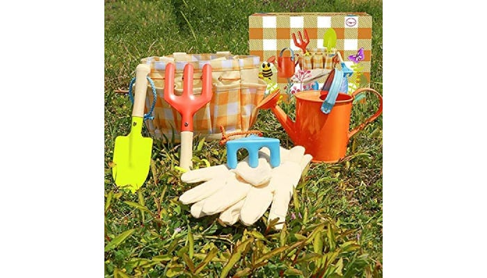 Colorful kids garden tools, gloves, and tote laid out on grass.