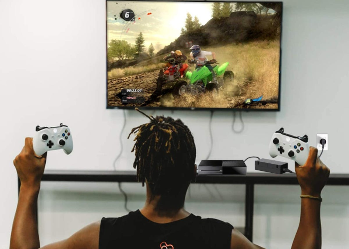 Man playing an Xbox One connected to a reliable power supply brick