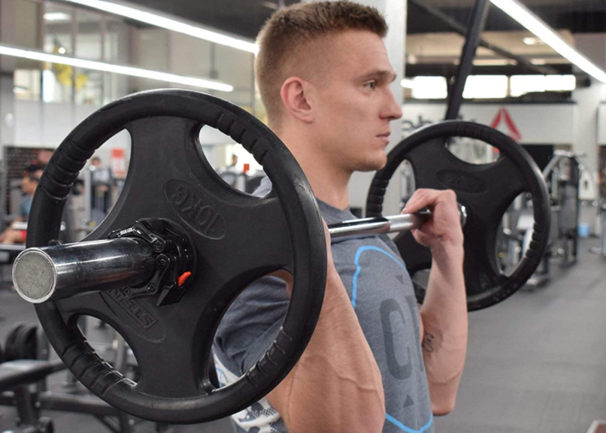 a man lifting a barbell in a gym