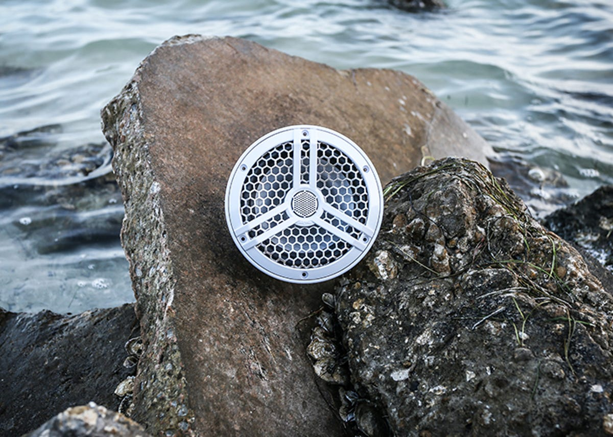 A boat speaker resting on a rock out by the shore.