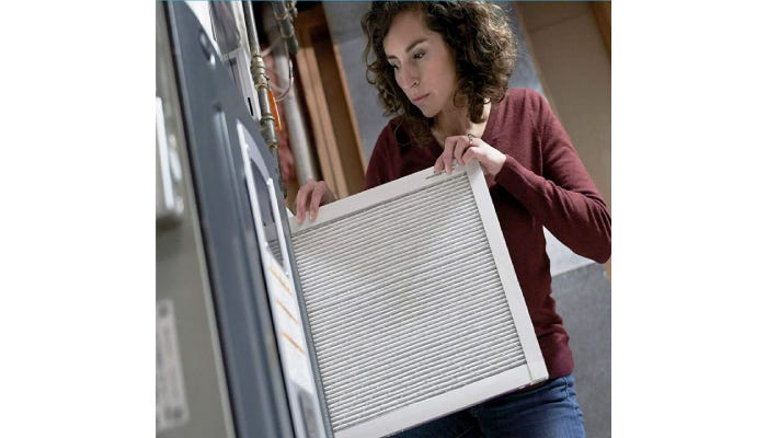 Woman installing new air filter