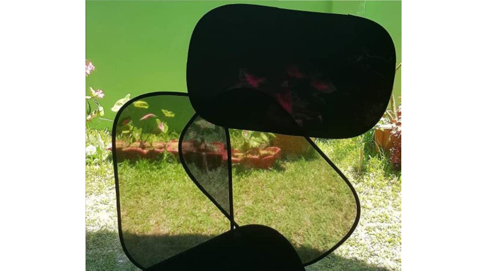 Set of four rectangular sunshades on a large window with a grassy yard in the background.