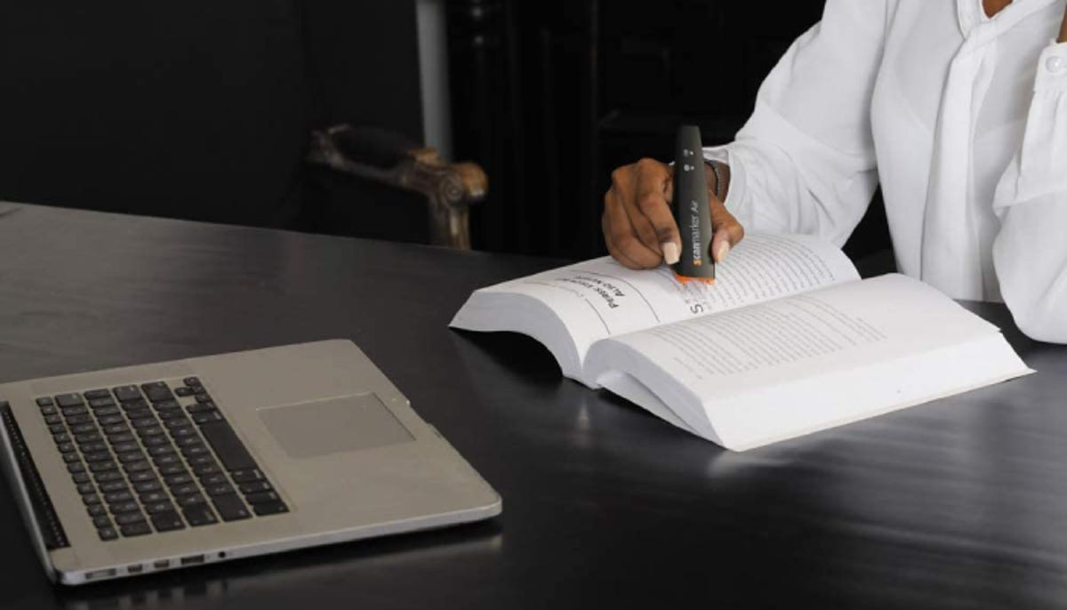 a woman using an OCR scanner pen over a book