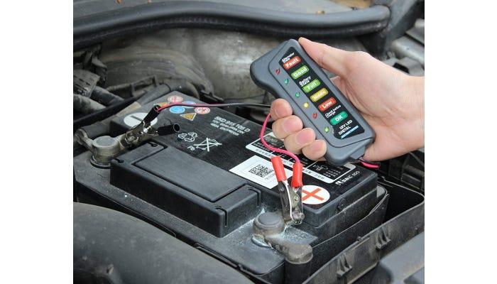 Hand holding battery tester over battery