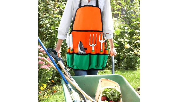 Person wearing an orange and green apron and pushing a wheelbarrow through a garden.