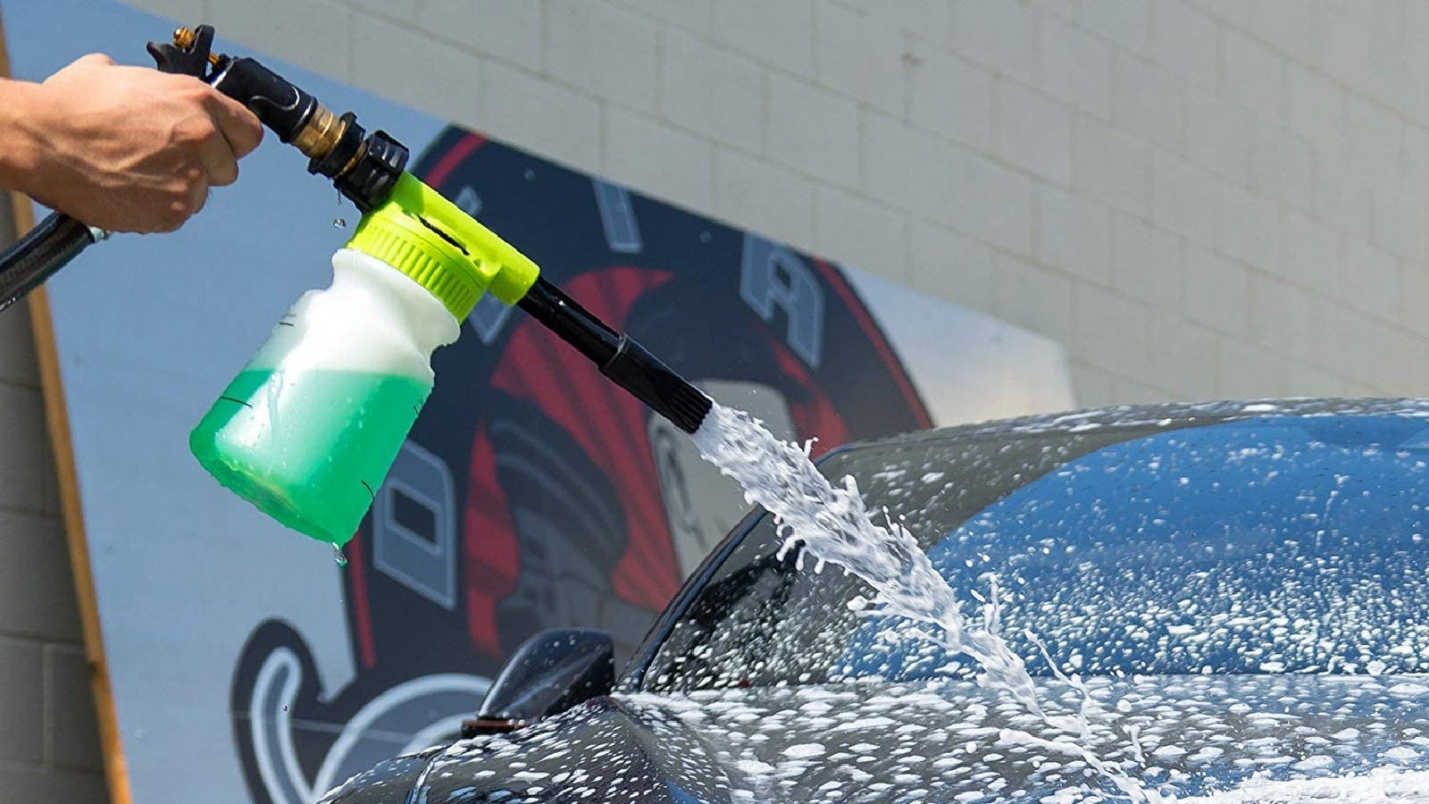 A person spraying a car with cleaning product using a foam sprayer.