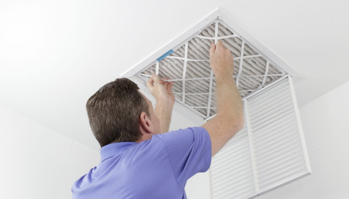 man removing a ceiling air filter