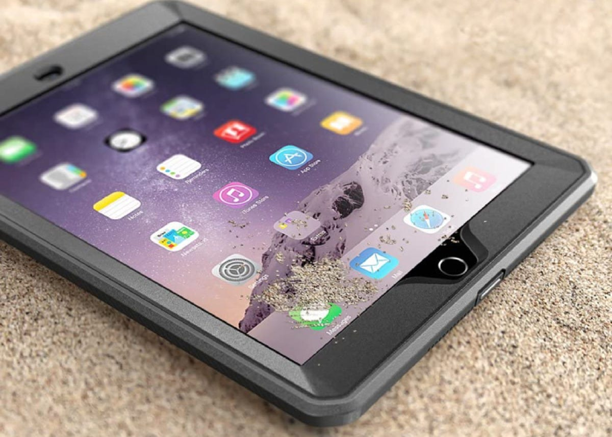 an iPad in a black case resting on sand