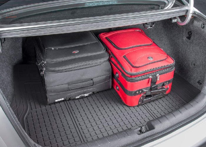 A rubber trunk mat in an open car trunk with two suitcases.