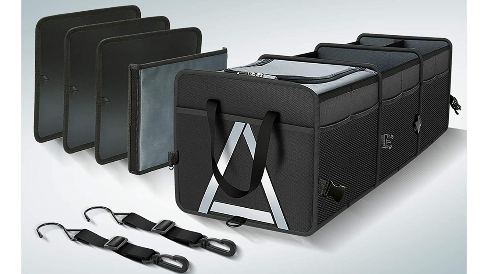 A black trunk storage organizer sitting next to two adjustable straps and four dividers.