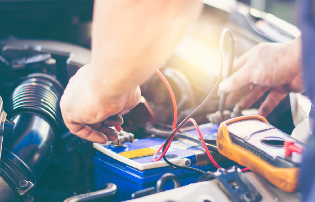 auto mechanic uses a device to check the voltage level in a car battery.