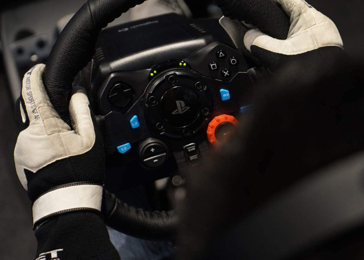 gloved hands gripping a PlayStation racing wheel playing a video game