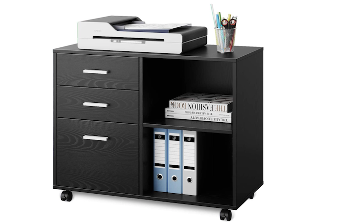 A horizontal black wooden file cabinet with three drawers, wheels, and two compartments containing books and binders, with a printer on top.