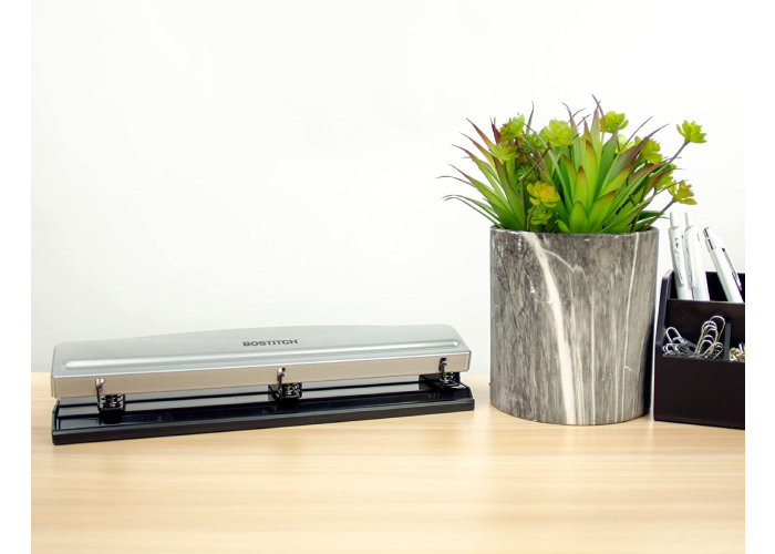 A three hole punch folded down on a desk next to a fake plant and basket with paper clips