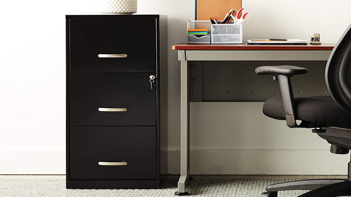 A vertical black filing cabinet with three drawers sitting next to a desk and swivel chair.