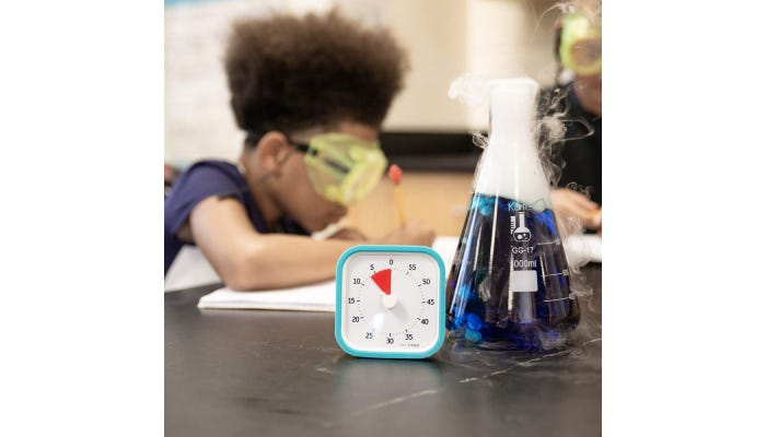 Timer in foreground, little girl with safety google finishing a test in background, also a beaker full of blue liquid