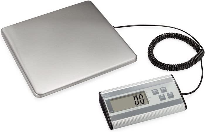 A classic floor luggage scale with an attached display device.