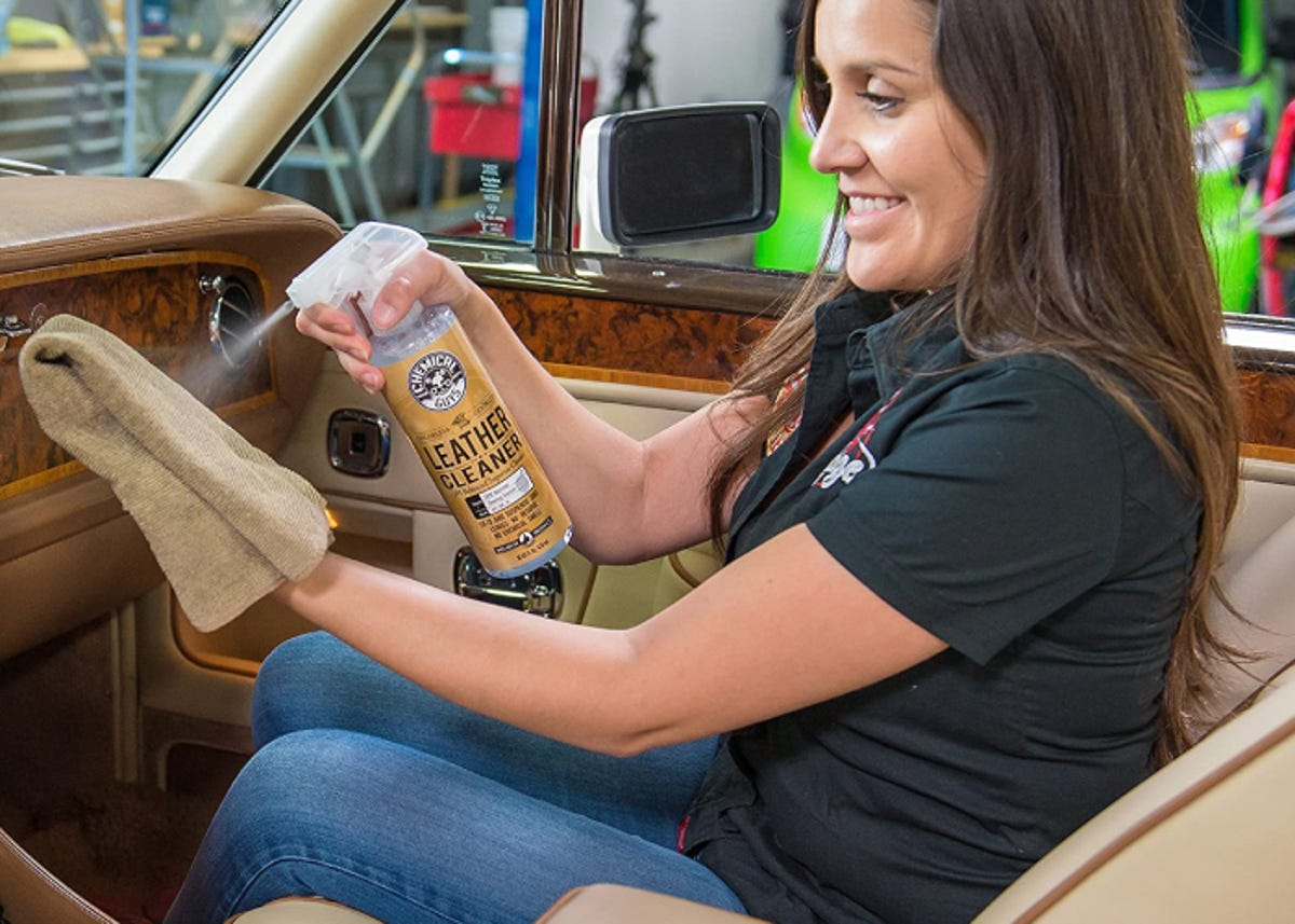 A woman spraying a towel with leather cleaner while sitting inside her car.