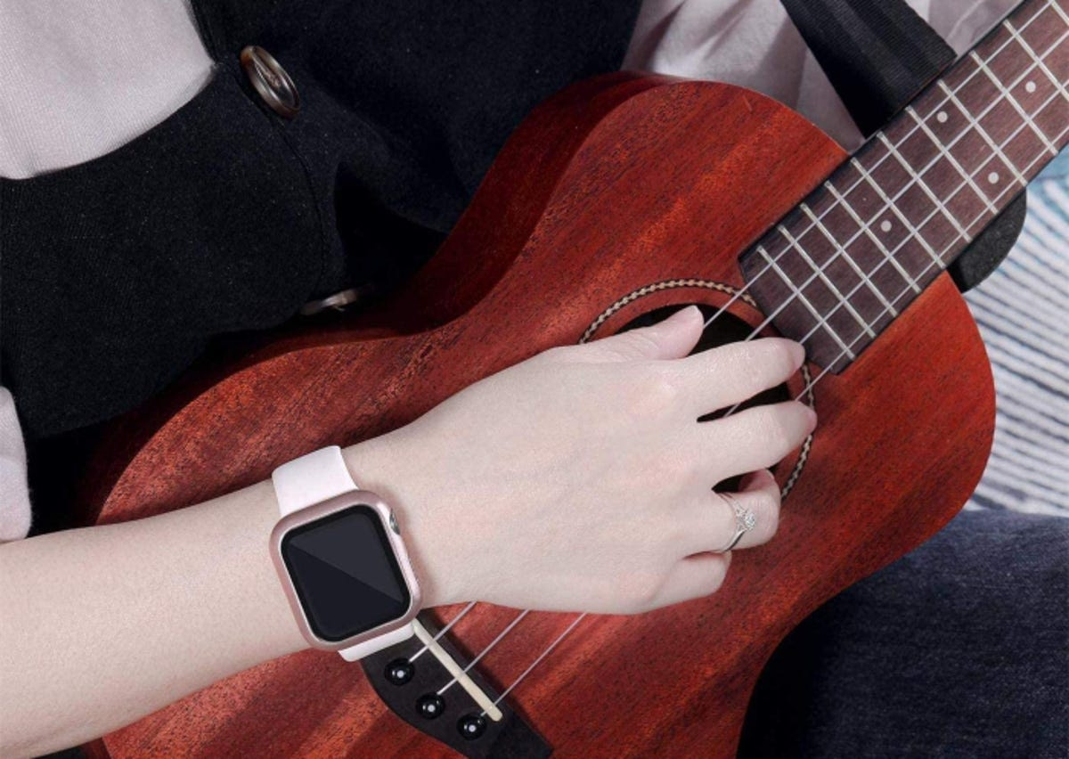 Person playing guitar while wearing an Apple Watch with a screen protection case