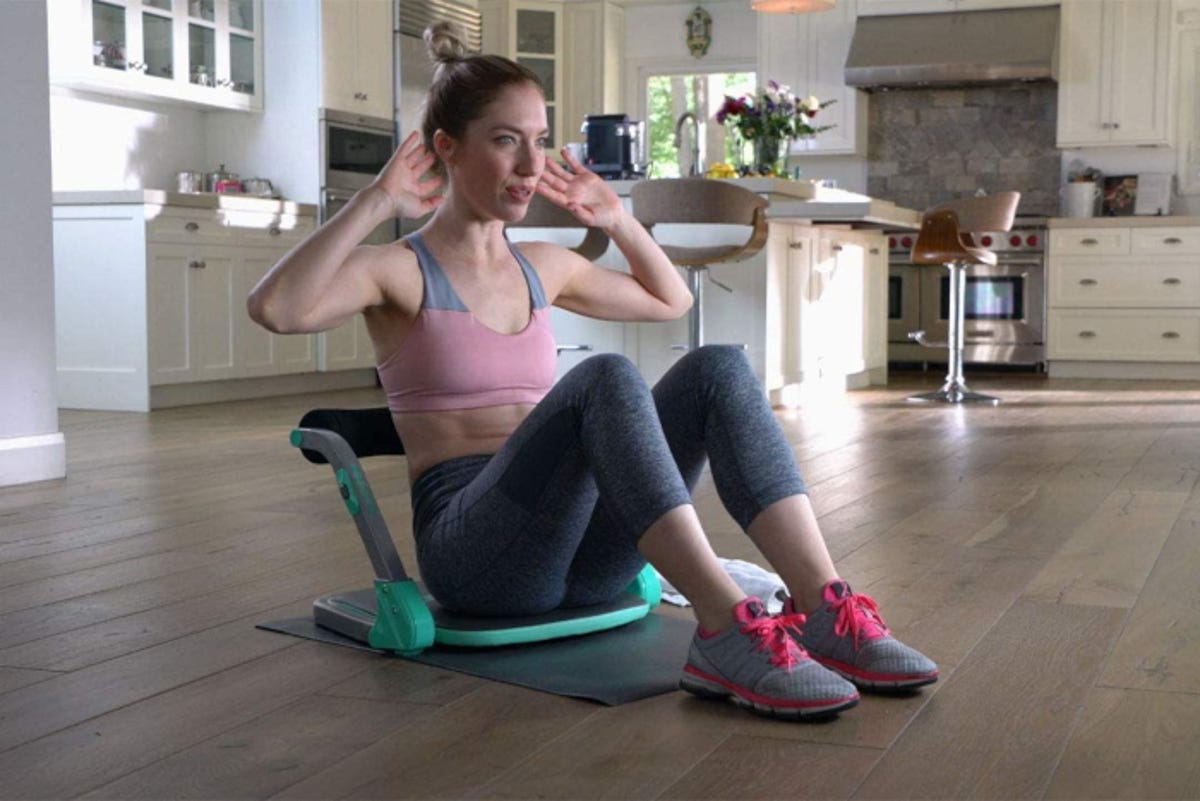 Woman doing abdominal crunches in home using padded multi-use home gym equipment