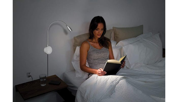 Woman lying in bed reading, light illuminated