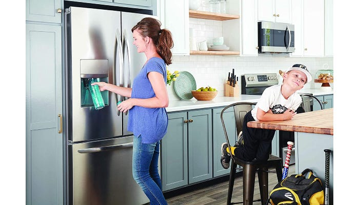 Woman filling water bottle from refrigerator water filter