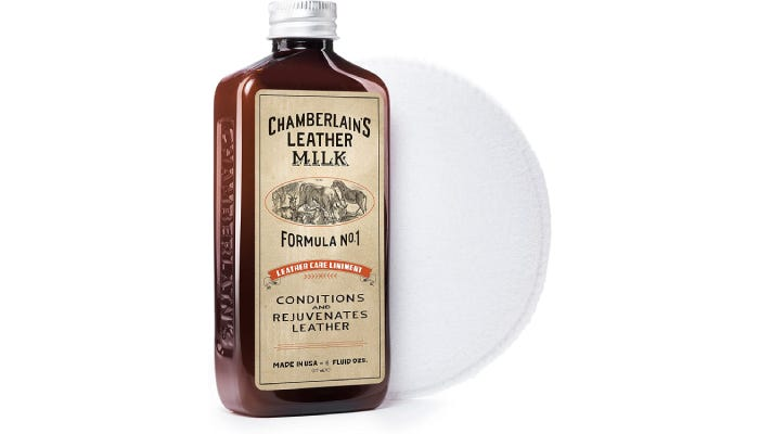 A bottle of leather conditioner sitting next to a cleaning pad.