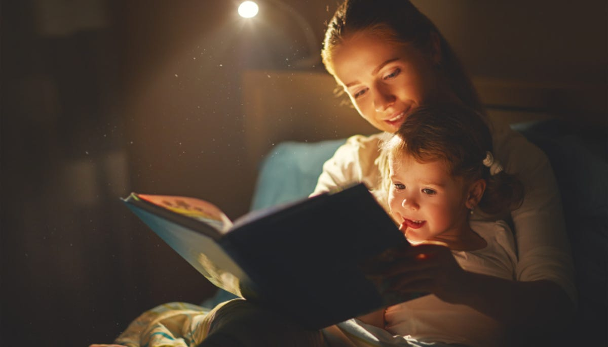mother and little girl reading a book in bed before going to sleep; a reading light is shining on them so they can see