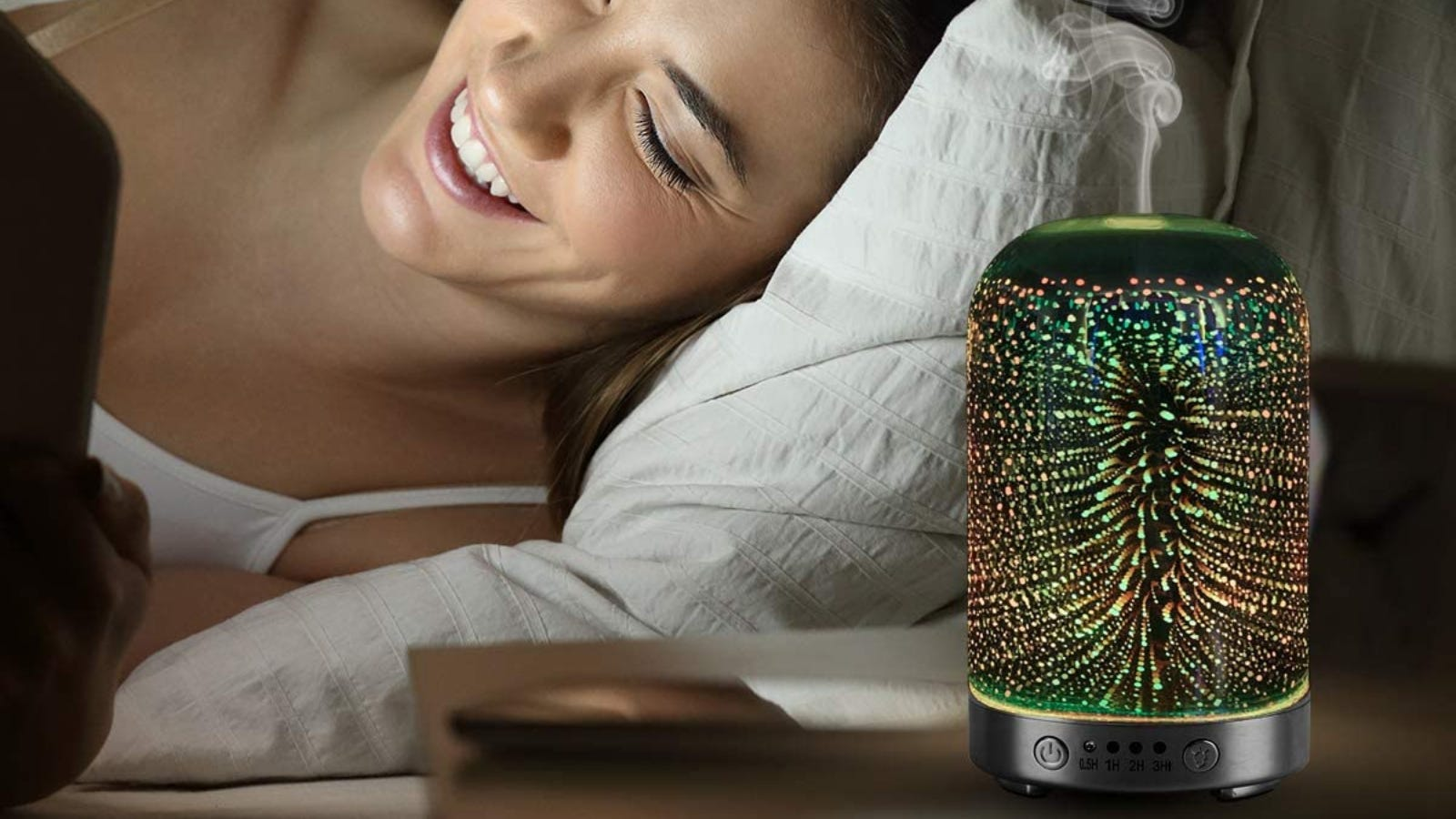 A women laying on a pillow is smiling at her phone and a colorful glass diffuser sits on her side table.